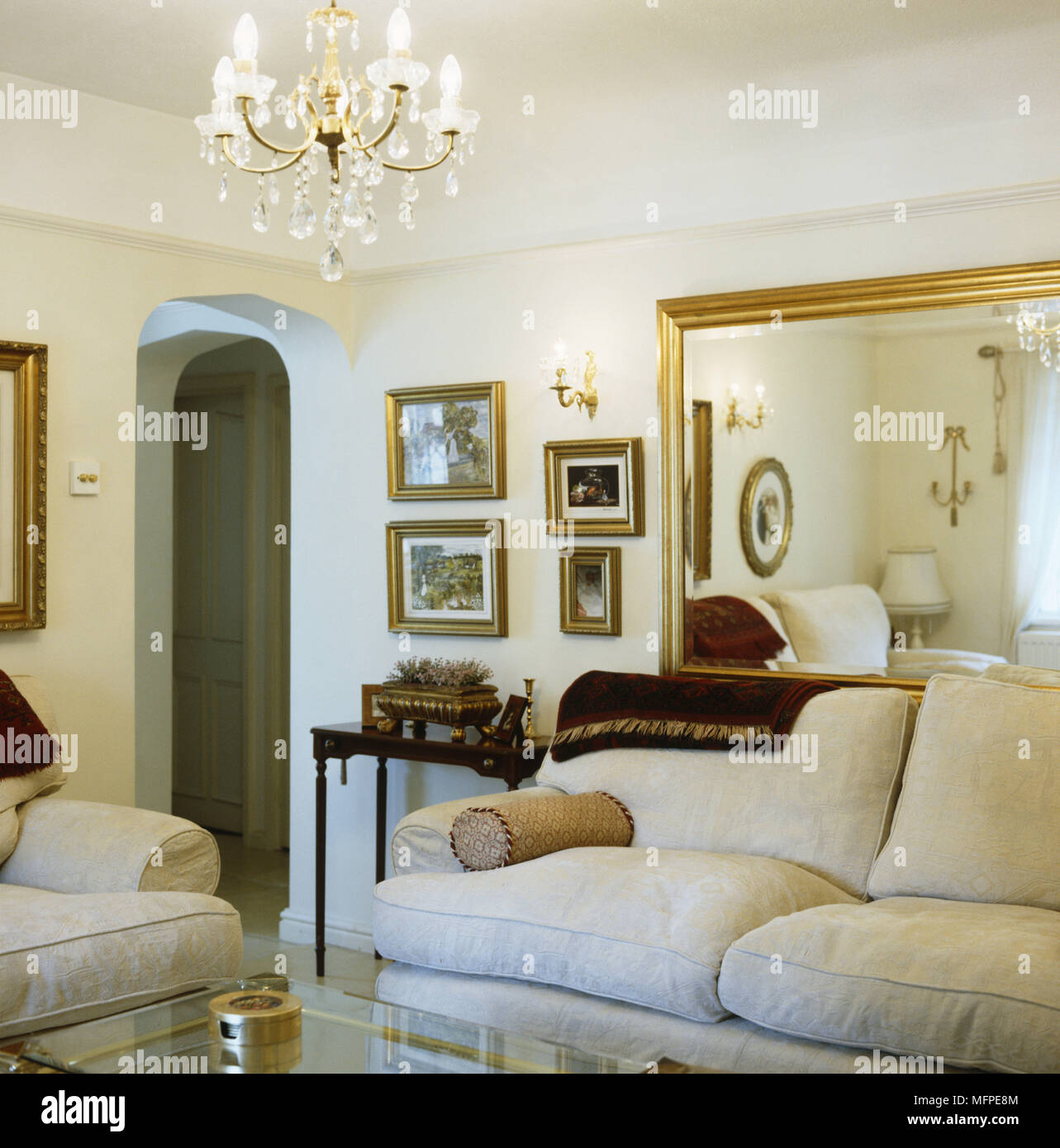 A traditional sitting room with a chandelier above two sofas in ...