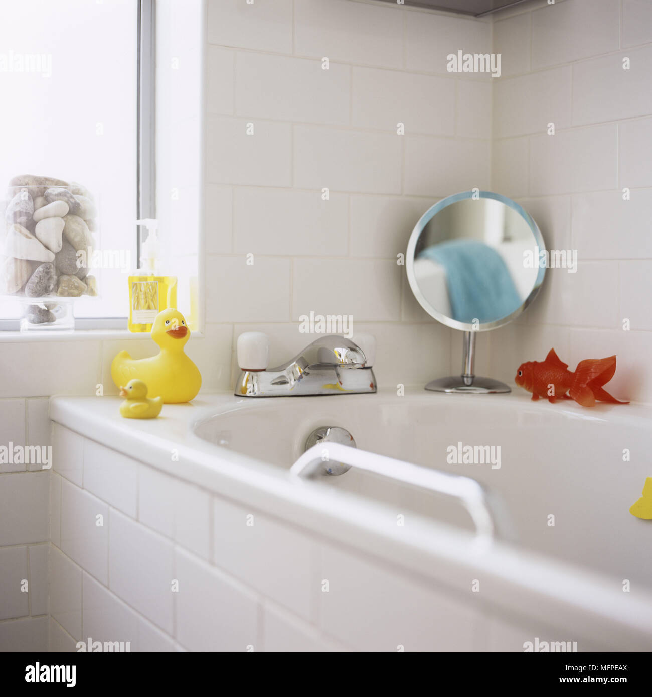 Bathroom with white tiling around the bath and walls with a yellow ...