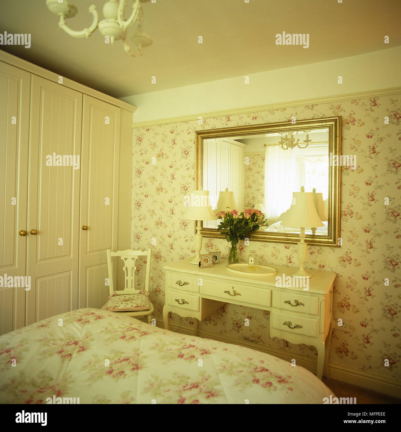 Floral decor and a large inbuilt wardrobe next to a mirror above a ...