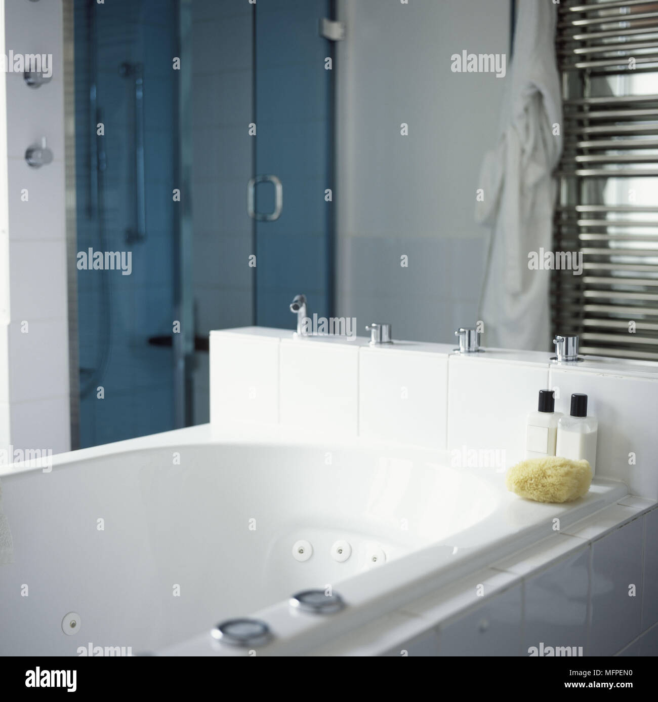 White bath in front of a shower with a blue screen and chrome ...