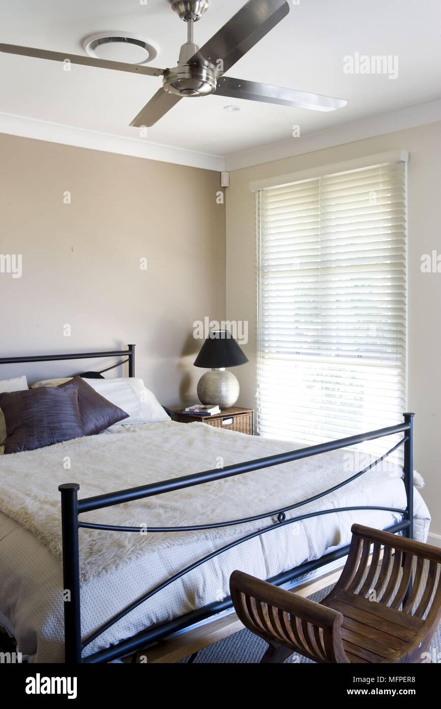 Ceiling Fan Above Metal Bed In Modern Bedroom Stock Photo 181818092