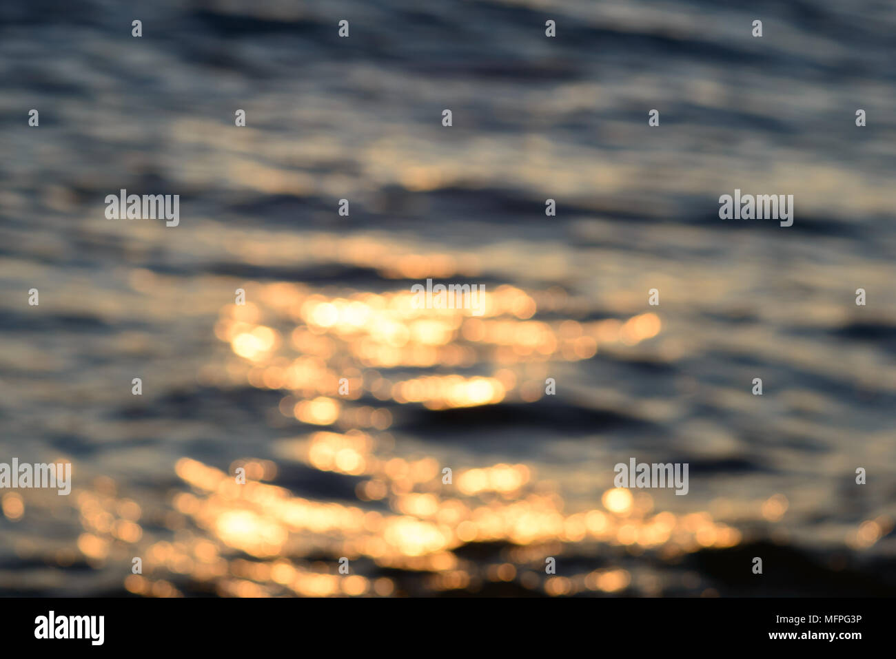 Blurred sea water in the evening light background - Stock Image