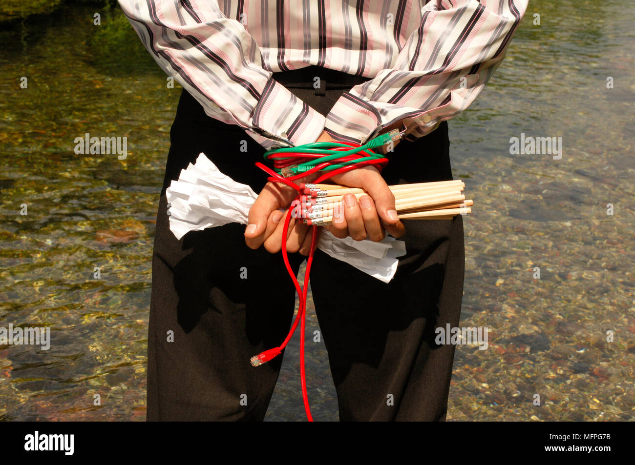 Mid section view of a man standing near a river with his hands tied behind his back   Ref: CRUSC_10015_018  Compulsory Credit: Stuart Cox/Photoshot - Stock Image