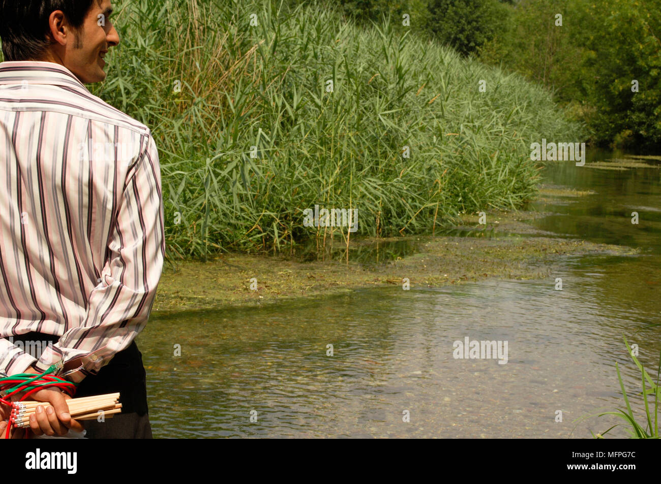 Rear view of a young man standing near a river with his hands tied behind his back   Ref: CRUSC_10015_019  Compulsory Credit: Stuart Cox/Photoshot - Stock Image