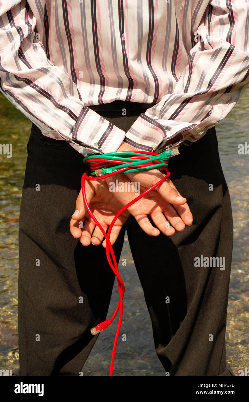 Mid section view of a man standing near a river with his hands tied behind his back   Ref: CRUSC_10015_020  Compulsory Credit: Stuart Cox/Photoshot - Stock Image