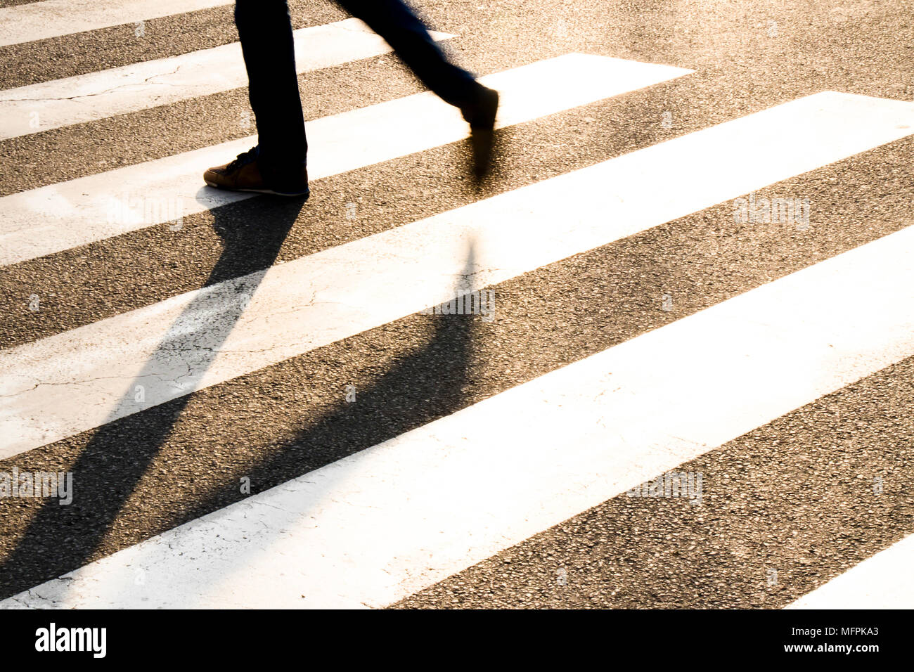 City street pedestrian crossing with legs of a man walking in motion blur making long shadows in  sunset - Stock Image