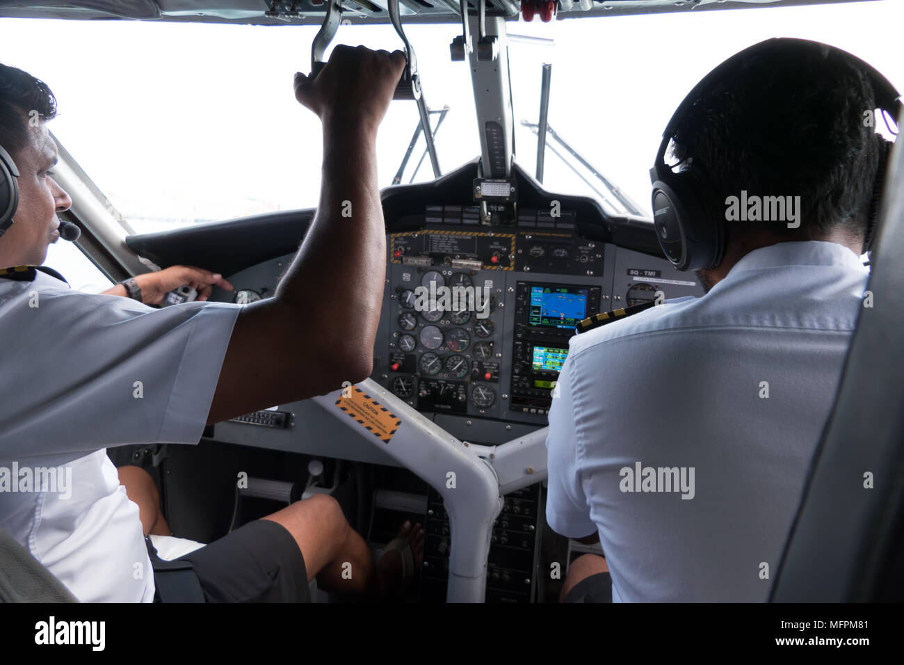 View of the cockpit of a small airplane flying in the sky. Team of pilots on plane, crew touching equipment and commands on dashboard. Aviation, trave - Stock Image