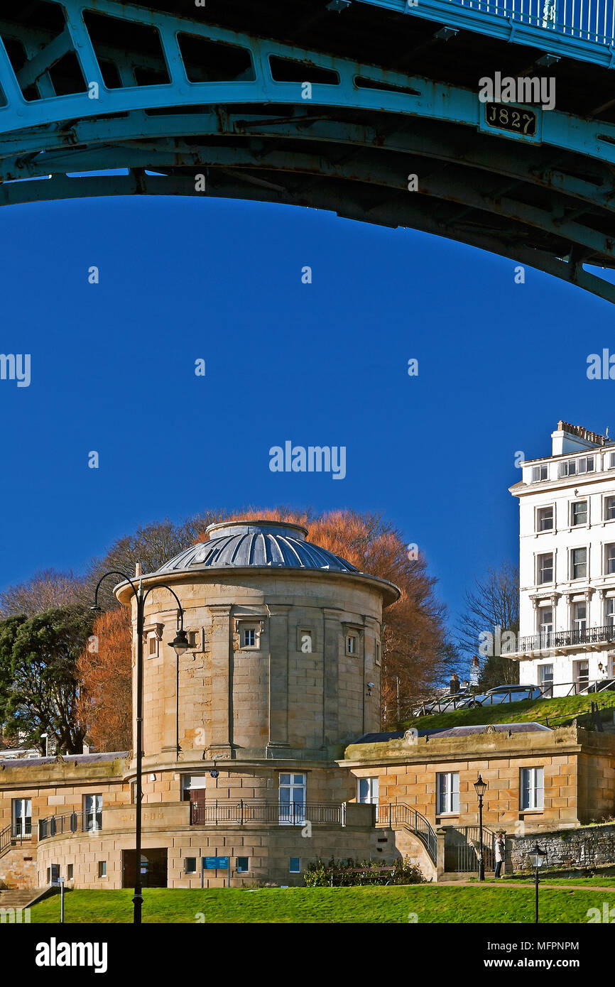 Scarborough's Rotunda Museum, lit by winter sunshine, nestles under one of the arches of the town's Spa Bridge. - Stock Image