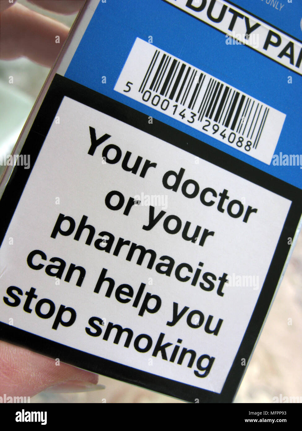Woman reading a cigarette packet with a warning on, indicating a doctor or pharmacist can help you to quit smoking - Stock Image