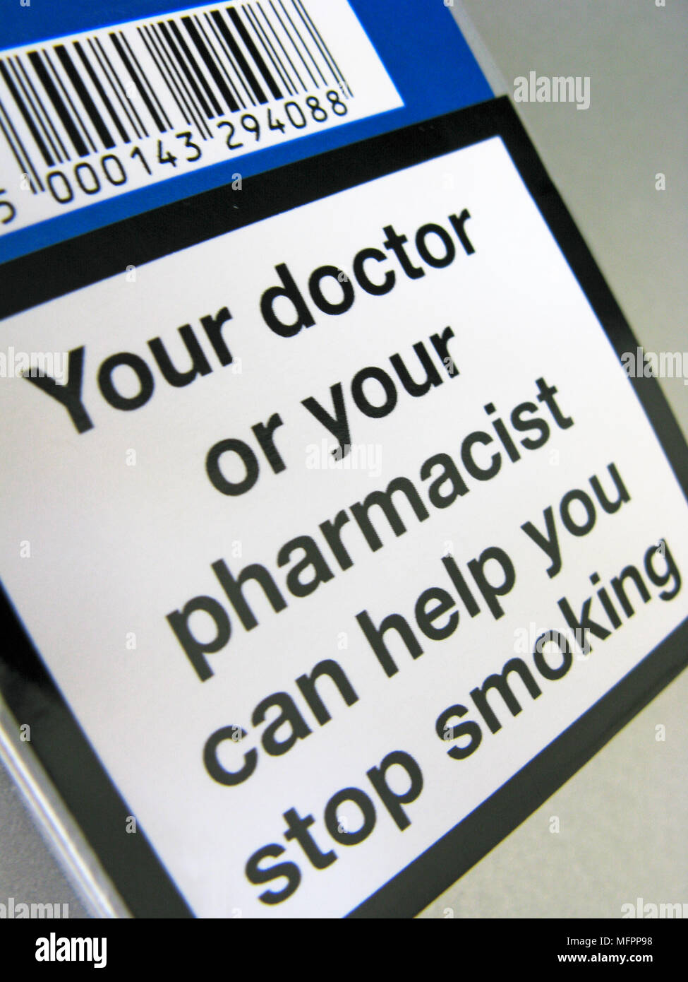 A cigarette packet with a warning on, indicating a doctor or pharmacist can help you to quit smoking - Stock Image