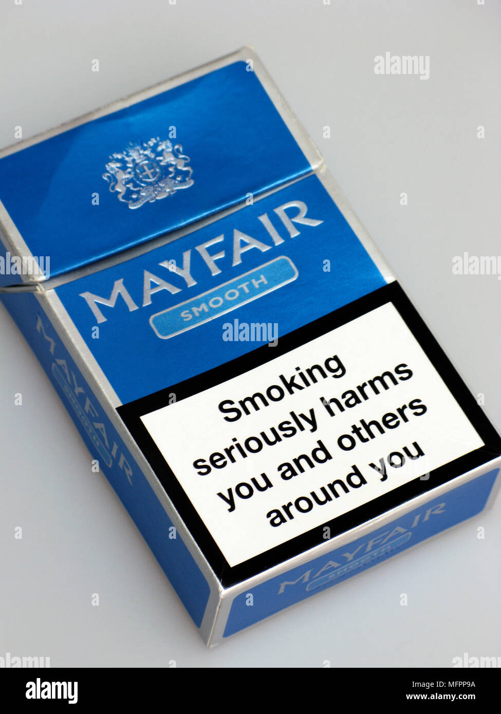 A cigarette packet with a warning on indicating a doctor or pharmacist can help you to quit smoking - Stock Image