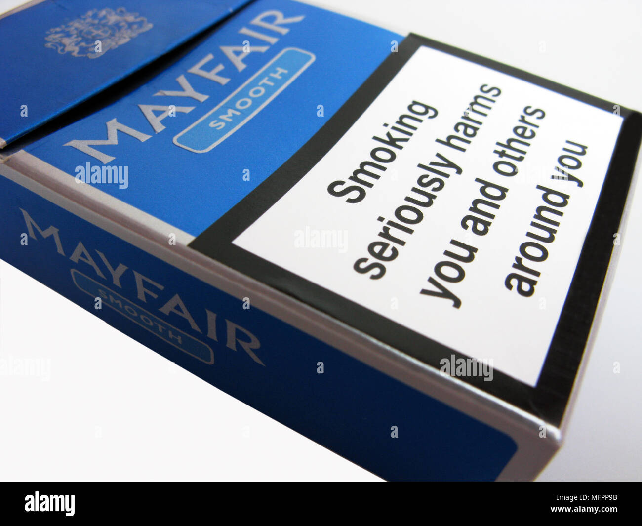 A cigarette packet with a warning on about seriously harming yourself by smoking - Stock Image