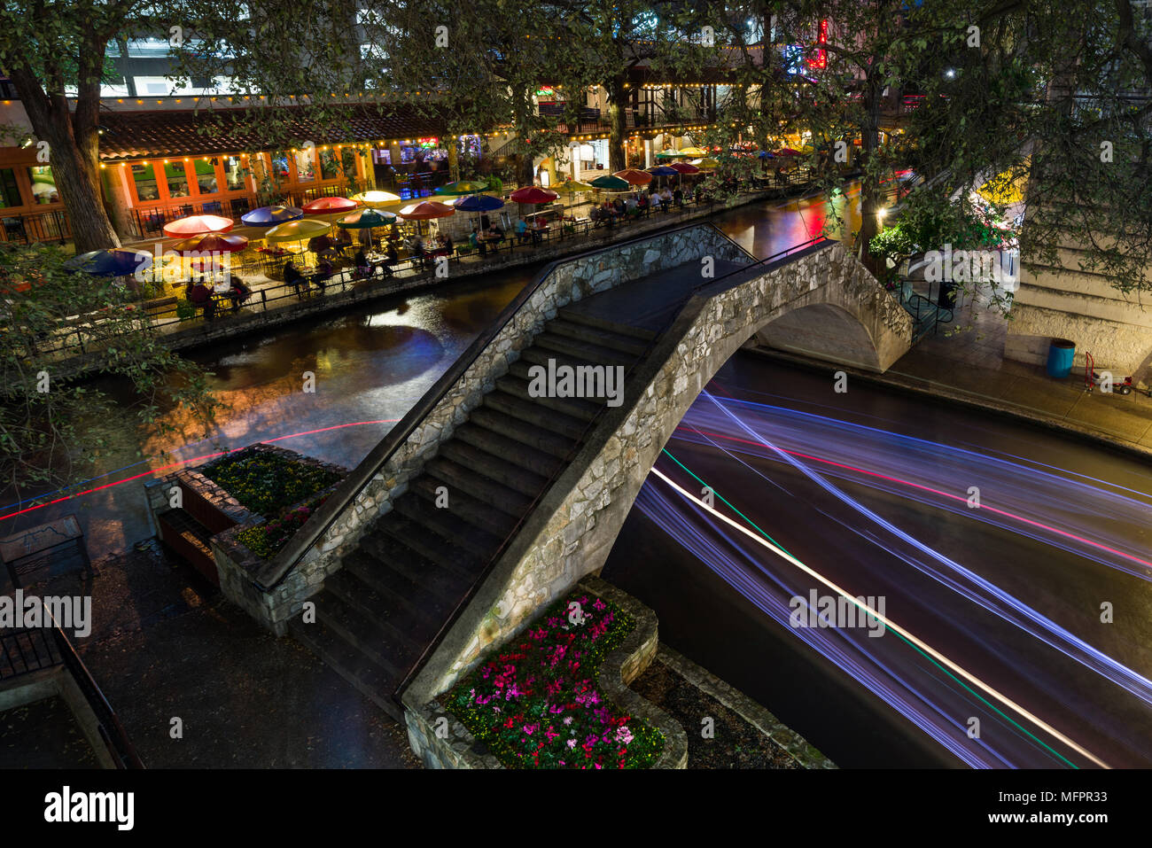 Part Of The San Antonio Riverwalk With People Walking Over A