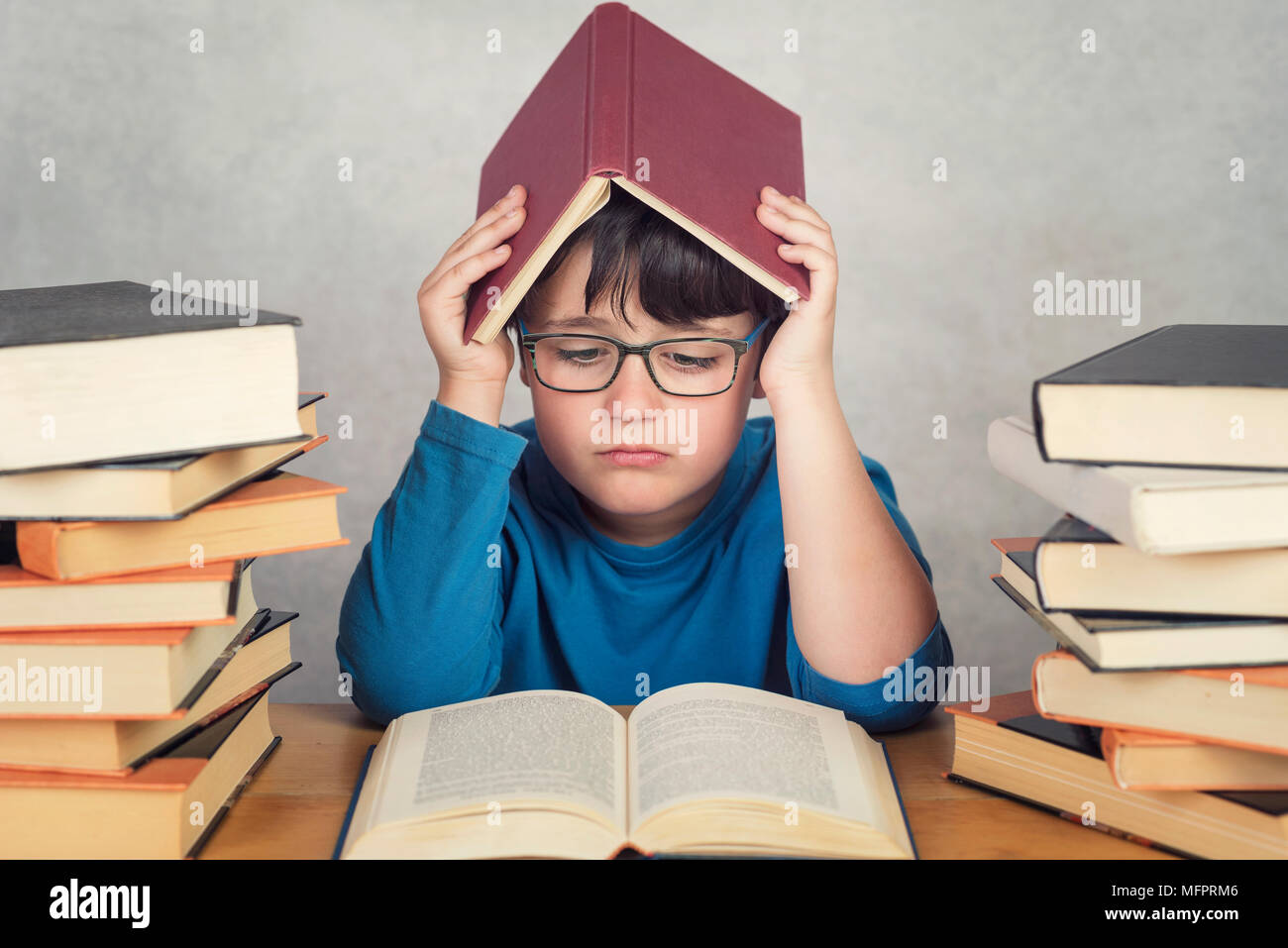 sad and pensive boy with books on a table - Stock Image
