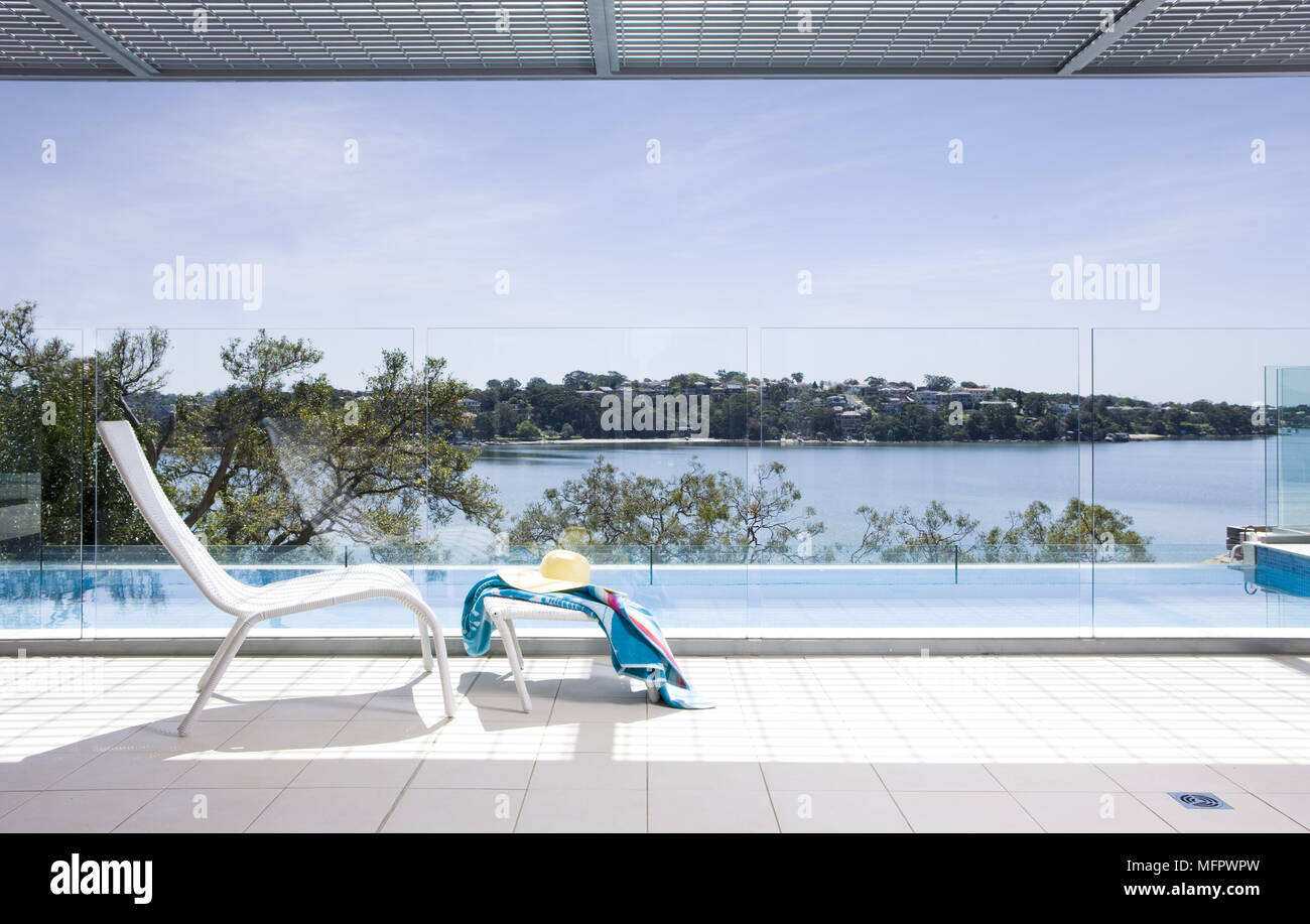Chair and footstool beside swimming pool - Stock Image