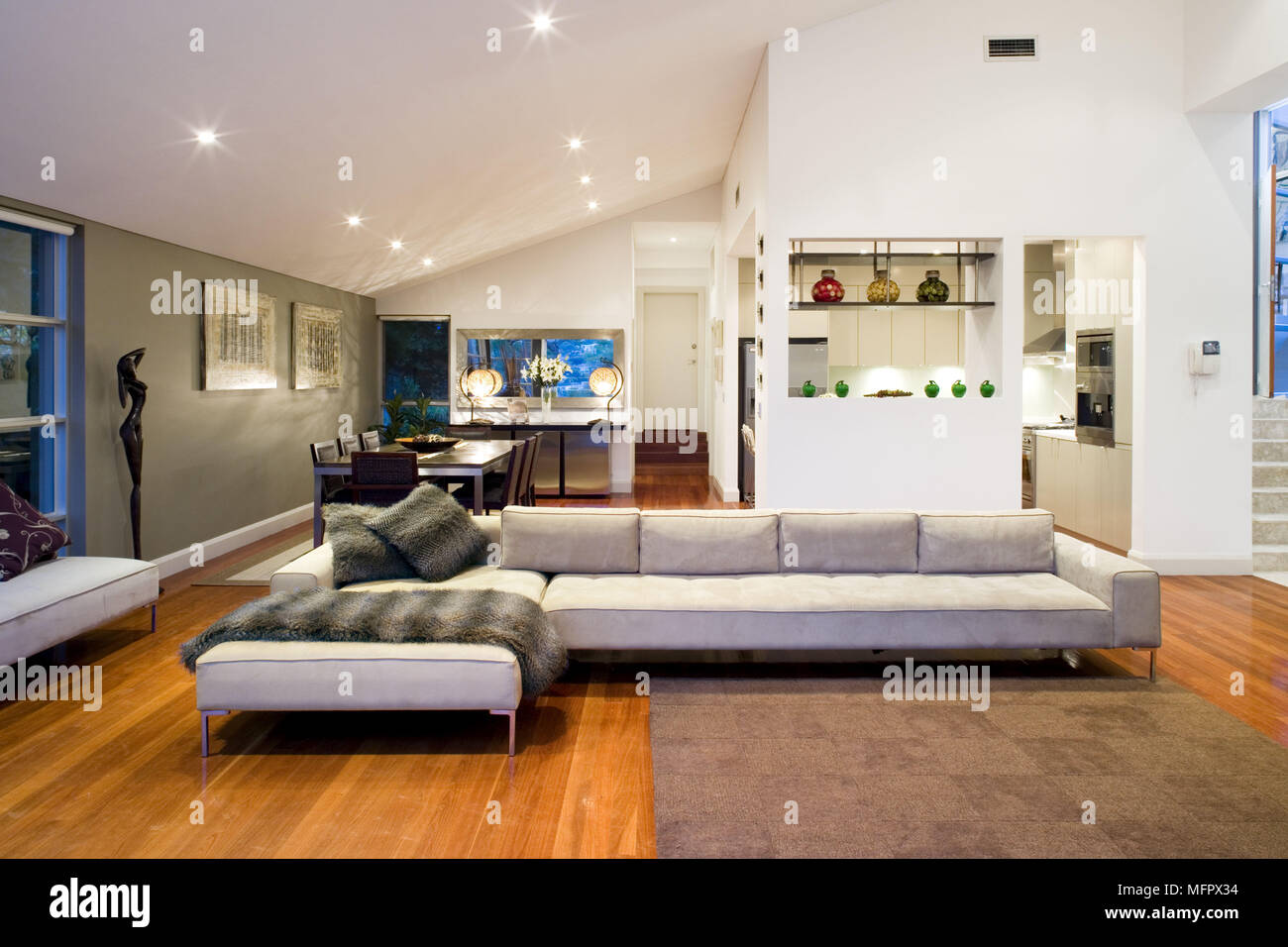 L shaped sofa in modern spacious open plan sitting room