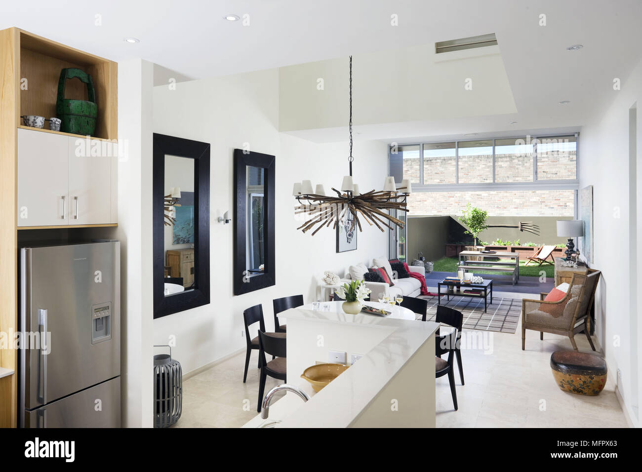 Modern open plan room with kitchen dining and sitting areas and open ...