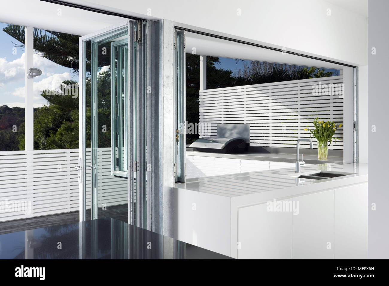 ba4aa9ee6caf Modern white kitchen with concertina door to balcony terrace Stock ...