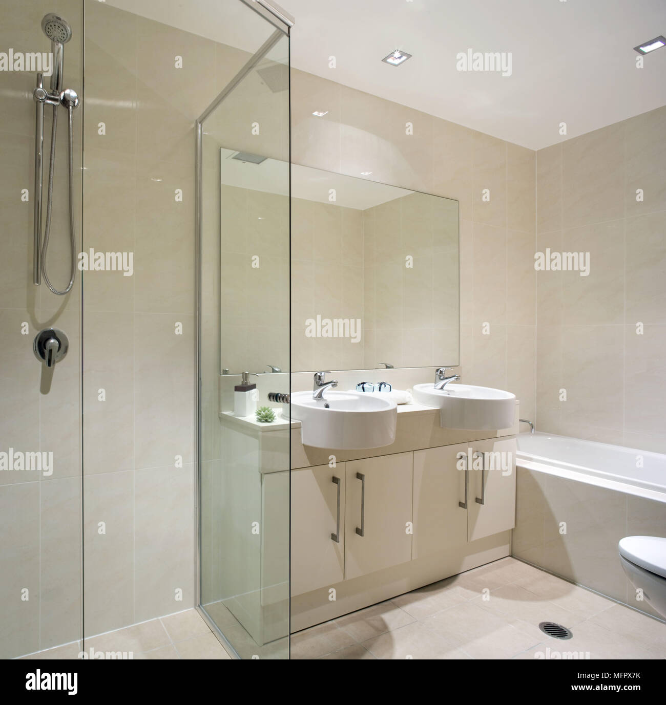 Pair of double washbasins set in cupboard unit next to shower unit ...