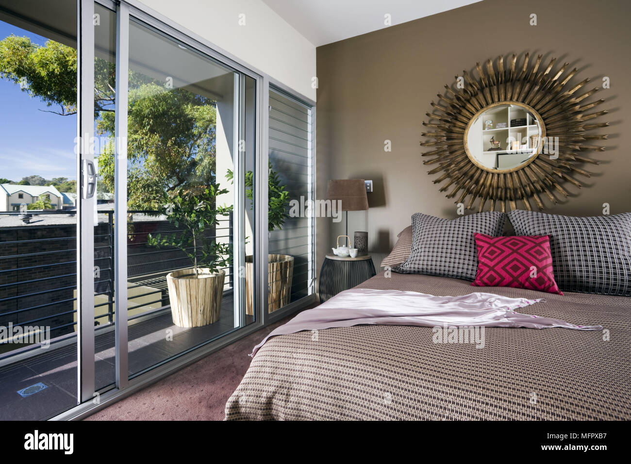 Sunray mirror above double bed in modern bedroom with glass patio