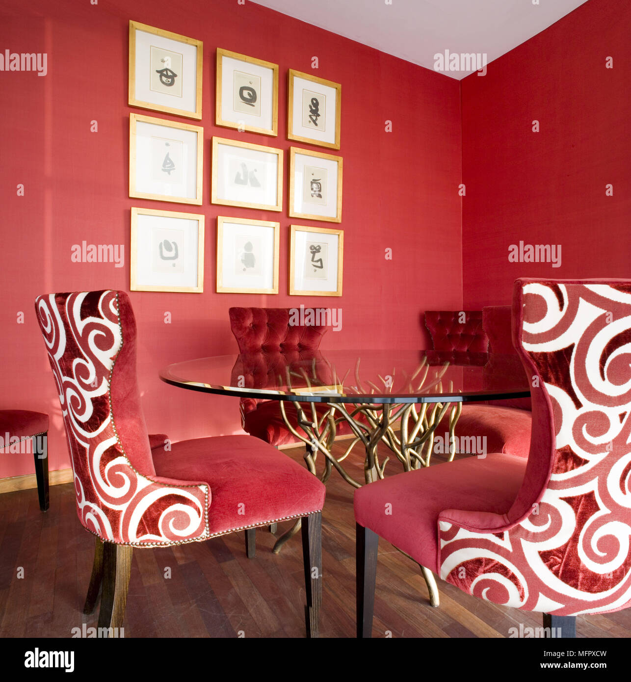 Upholstered chairs with white pattern at glass topped table in modern red dining room Stock Photo