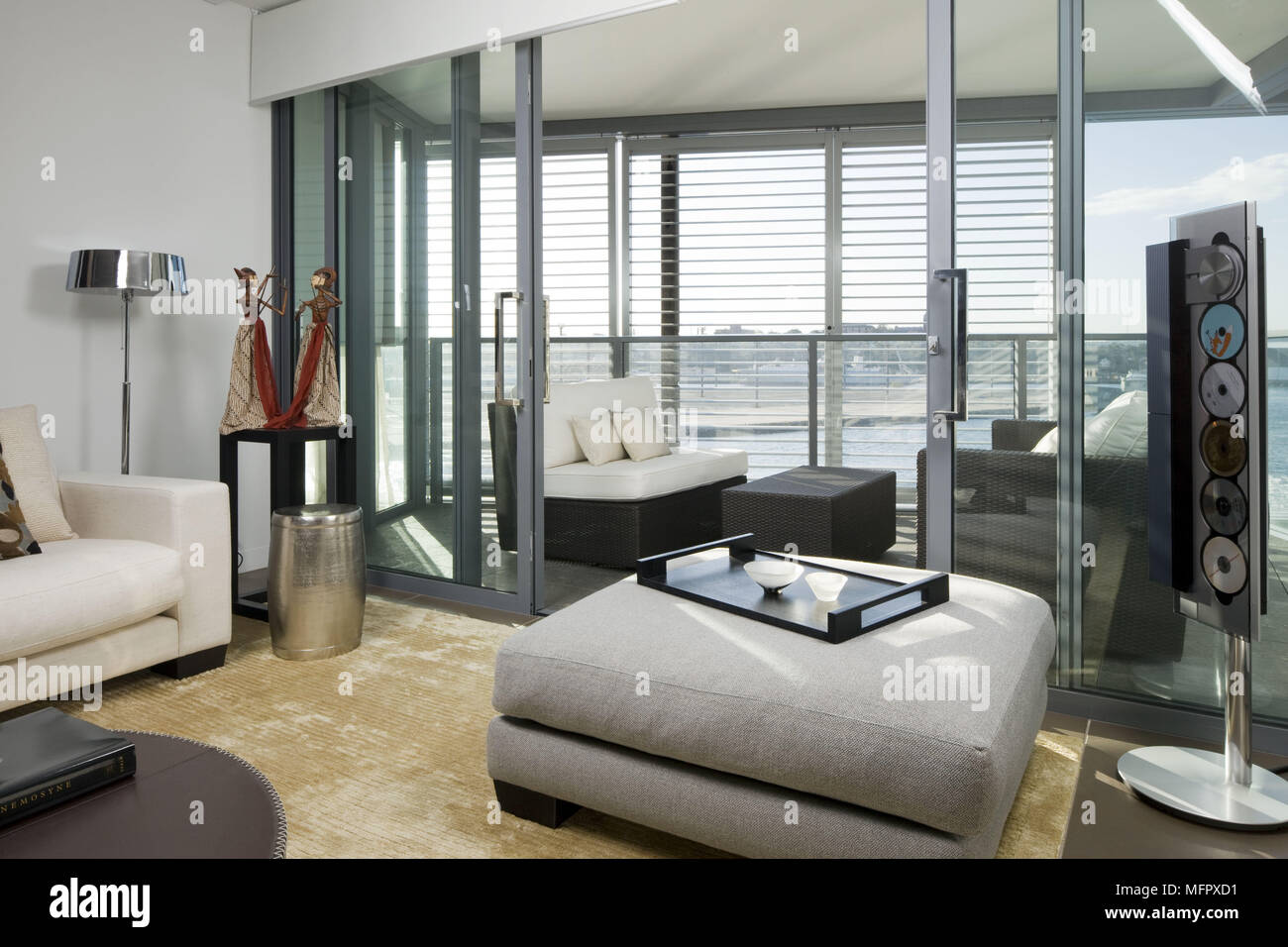 05656be8b800 Upholstered ottoman in modern sitting room with sliding doors to balcony  terrace