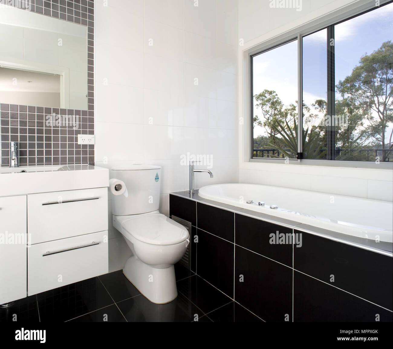 Washbasin set in cupboard unit next to toilet and bathtub in modern white bathroom Stock Photo