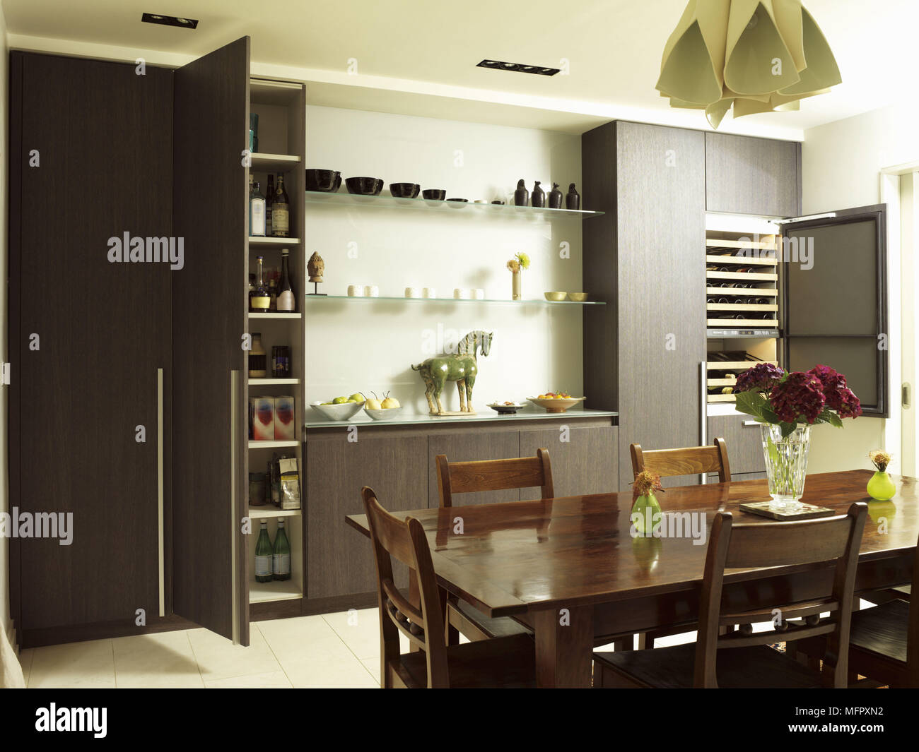 Dining Table And Chairs In Front Of Central Island Unit In Spacious Kitchen With Wood Units With Open Cupboard Door Stock Photo Alamy