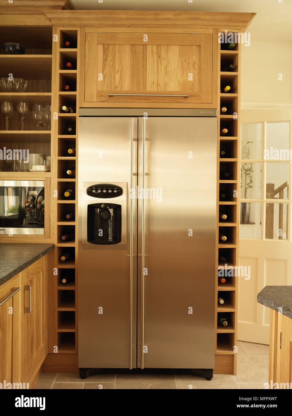 Stainless Steel Fridge And Built In Wine Rack Storage In Kitchen With Wood  Fitted Units