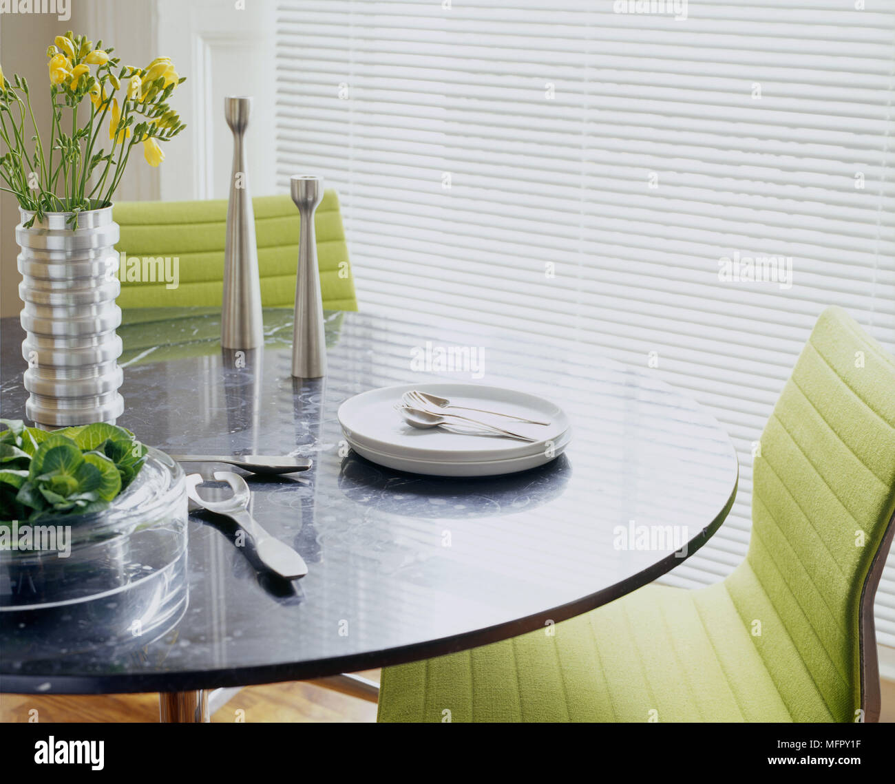A Modern Dining Room With Round Table Upholstered Lime Green Chairs White Tableware Steel Vases Stock Photo Alamy