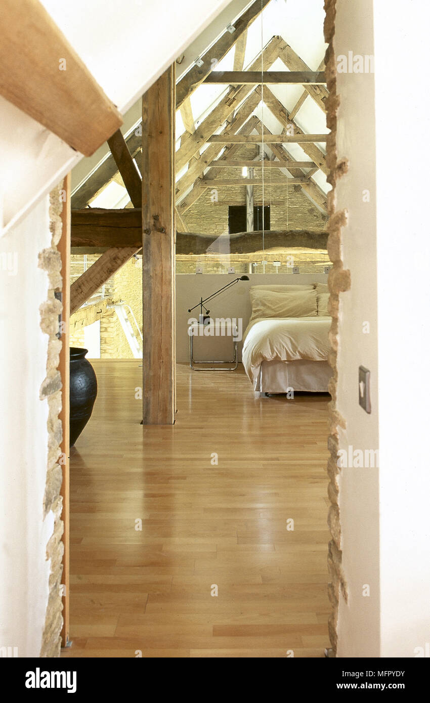 View Through Doorway To A Loft Bedroom In Converted Stone Barn With Wood Floor Exposed Roof Trusses And Double Bed Stock Photo 181828023