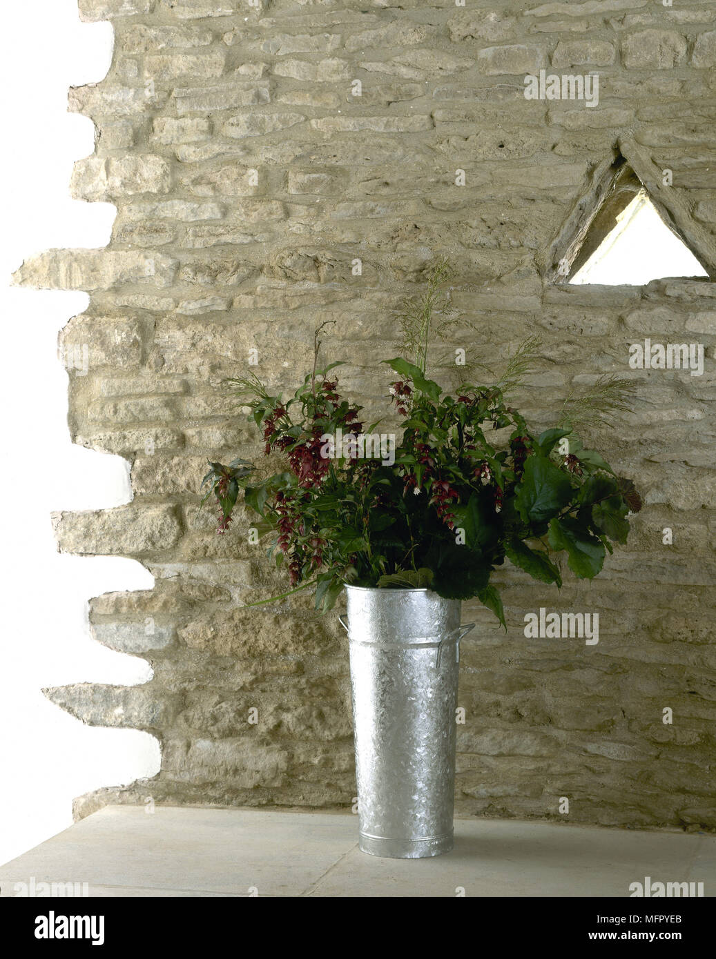 An exposed stone wall detail with a triangular window and a bouquet of flowers in a galvanized steel vase. - Stock Image