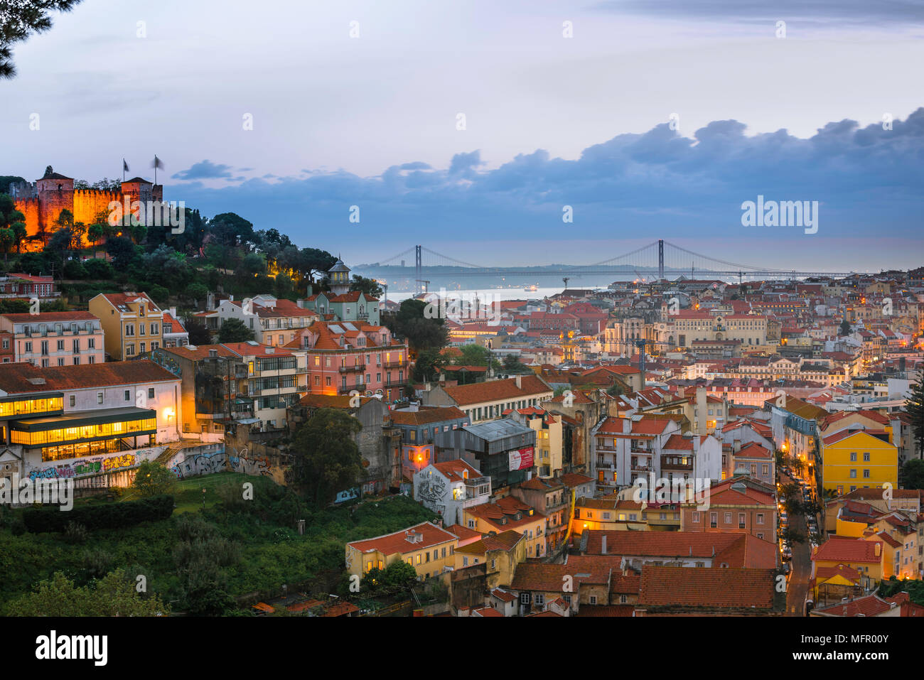 Lisbon cityscape, view across the rooftops of the Mouraria in the center of Lisbon towards the River Tagus and the Ponte 25 de Abril bridge, Portugal. Stock Photo