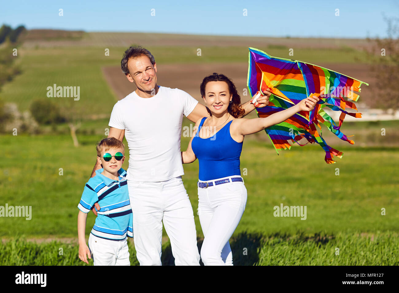 Happy family with a kite on nature in spring, summer. - Stock Image