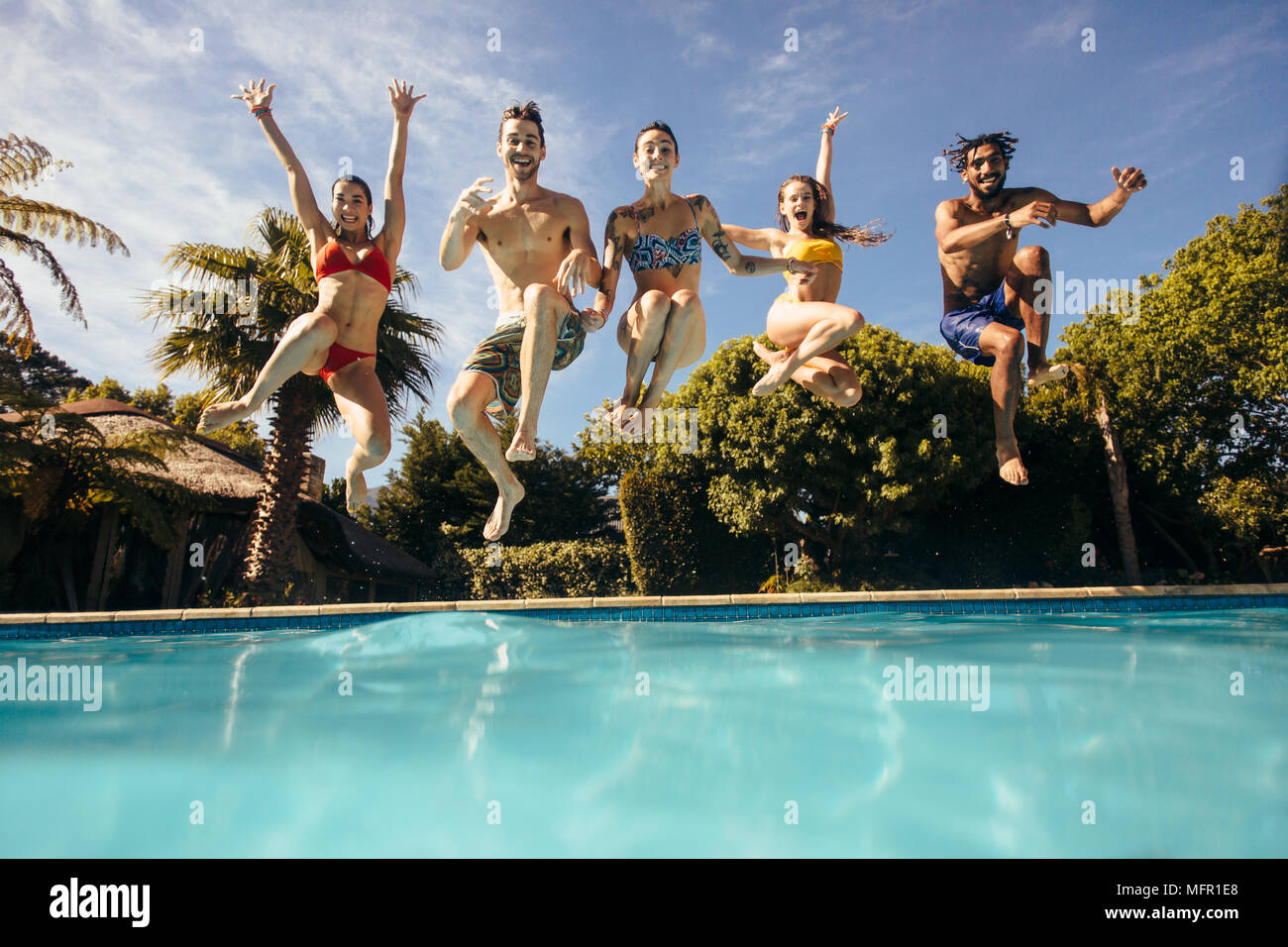 Group Of Crazy Young People Jumping Into A Swimming Pool Friends Having Fun At Holiday Resort