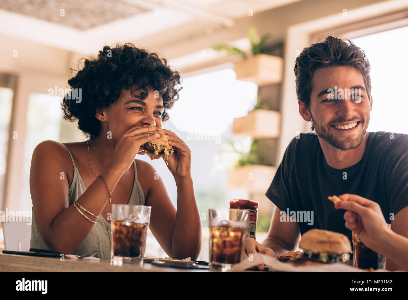 Young woman with friends eating burger at restaurant. Young people hanging out at a cafe chatting and eating burgers. - Stock Image