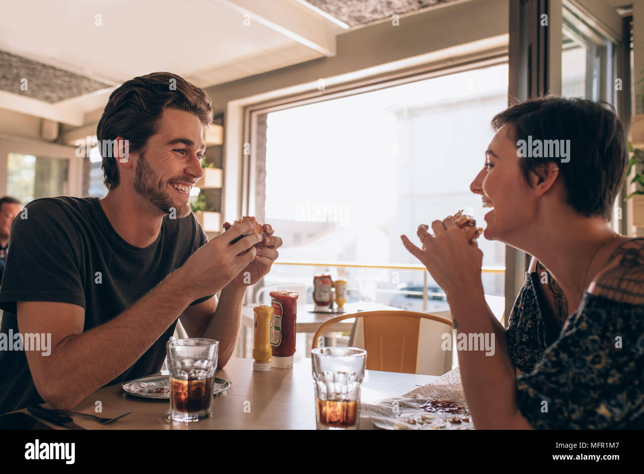 Happy couple eating burger and enjoying in cafe. Young man talking with his girlfriend and smiling while eating at a restaurant. - Stock Image