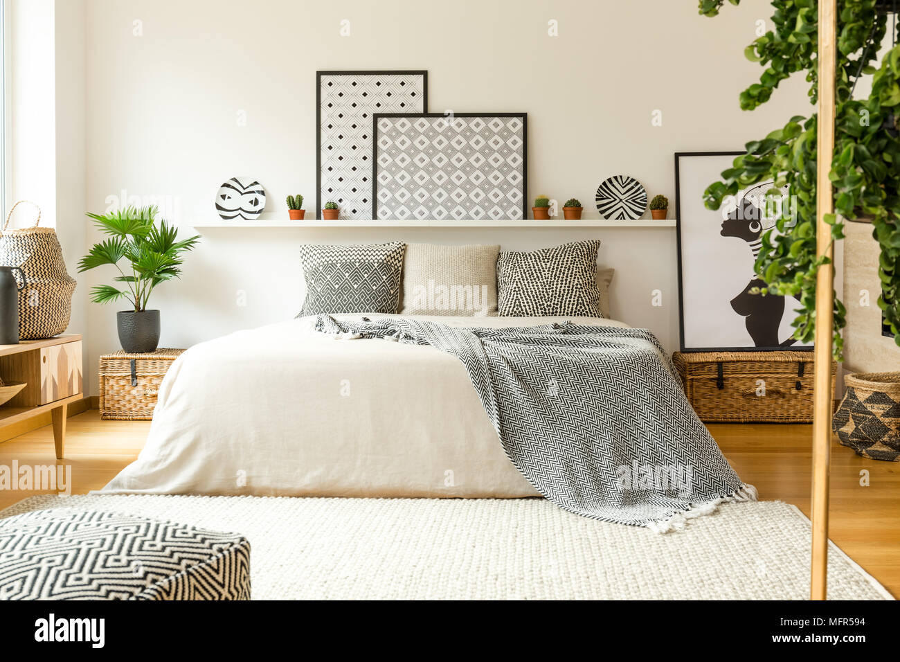 Warm bedroom interior with a comfy bed, patterned blanket and pillows, plants and modern graphics - Stock Image