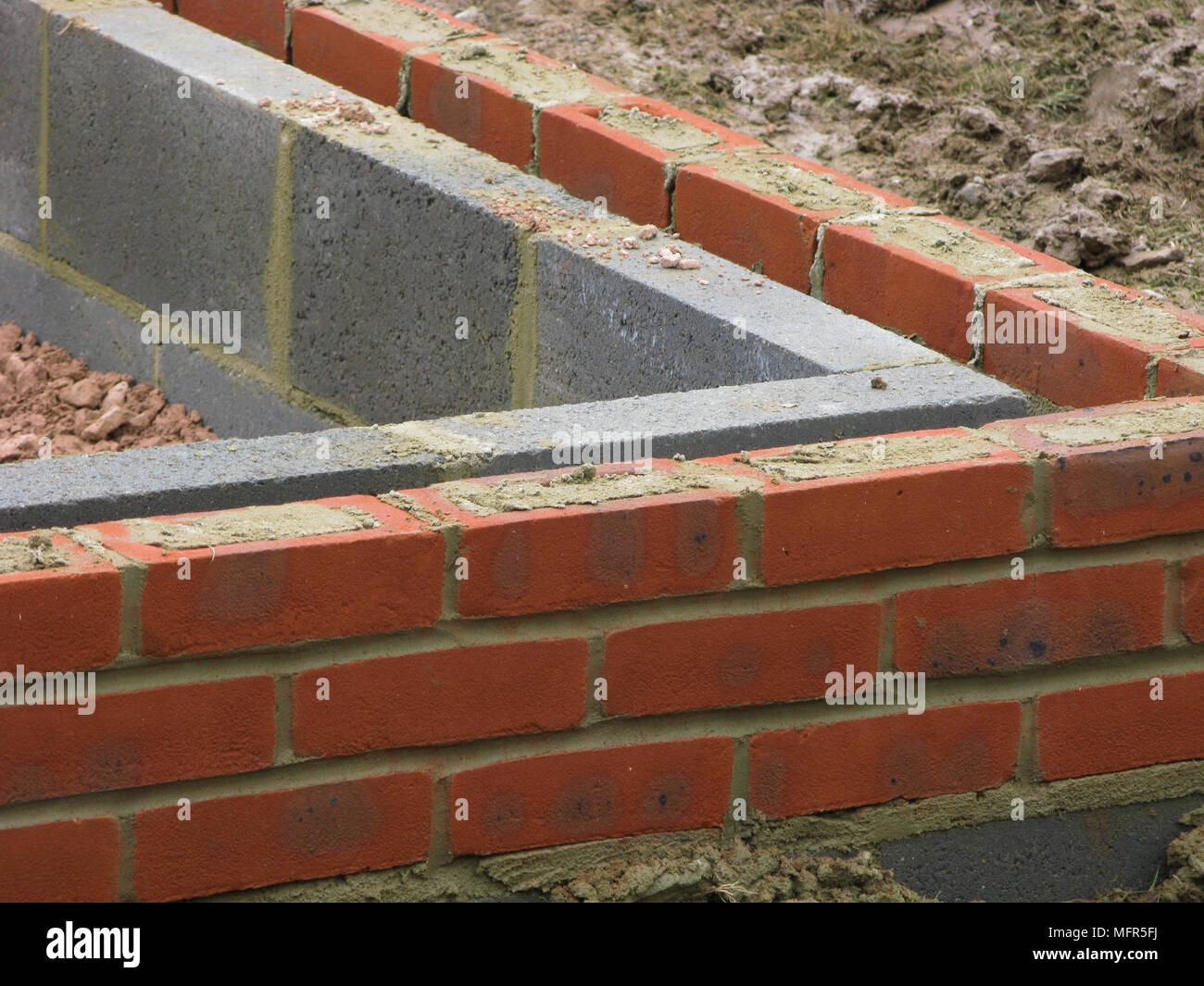 Bricks & thermalite bricks built up to the damp course in a wall - Stock Image
