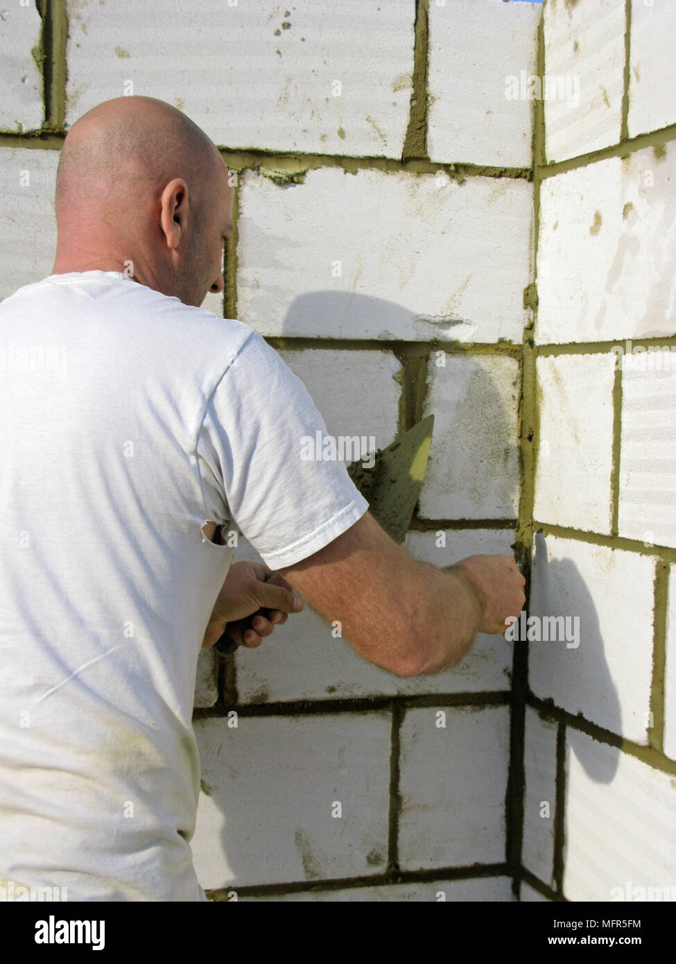 Builder / construction worker working on a brick wall