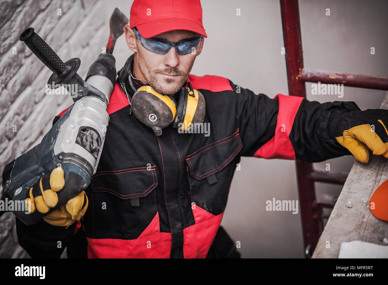 Caucasian Construction Worker with Heavy Duty Power Tool. - Stock Image