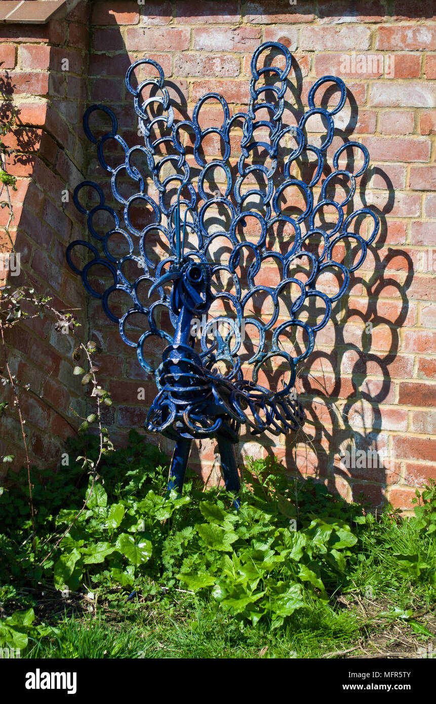 Metal sculpture displayed outdoors in the gardens of Nature in Art, a museum dedicated to art inspired by nature; Twigworth, Gloucester, UK - Stock Image
