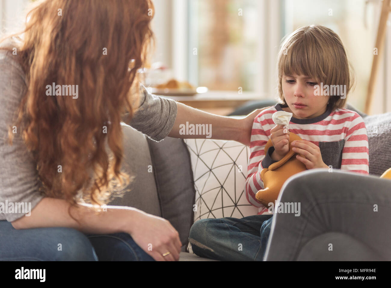 Caring mother supporting her sick son staying at home with a cold Stock Photo