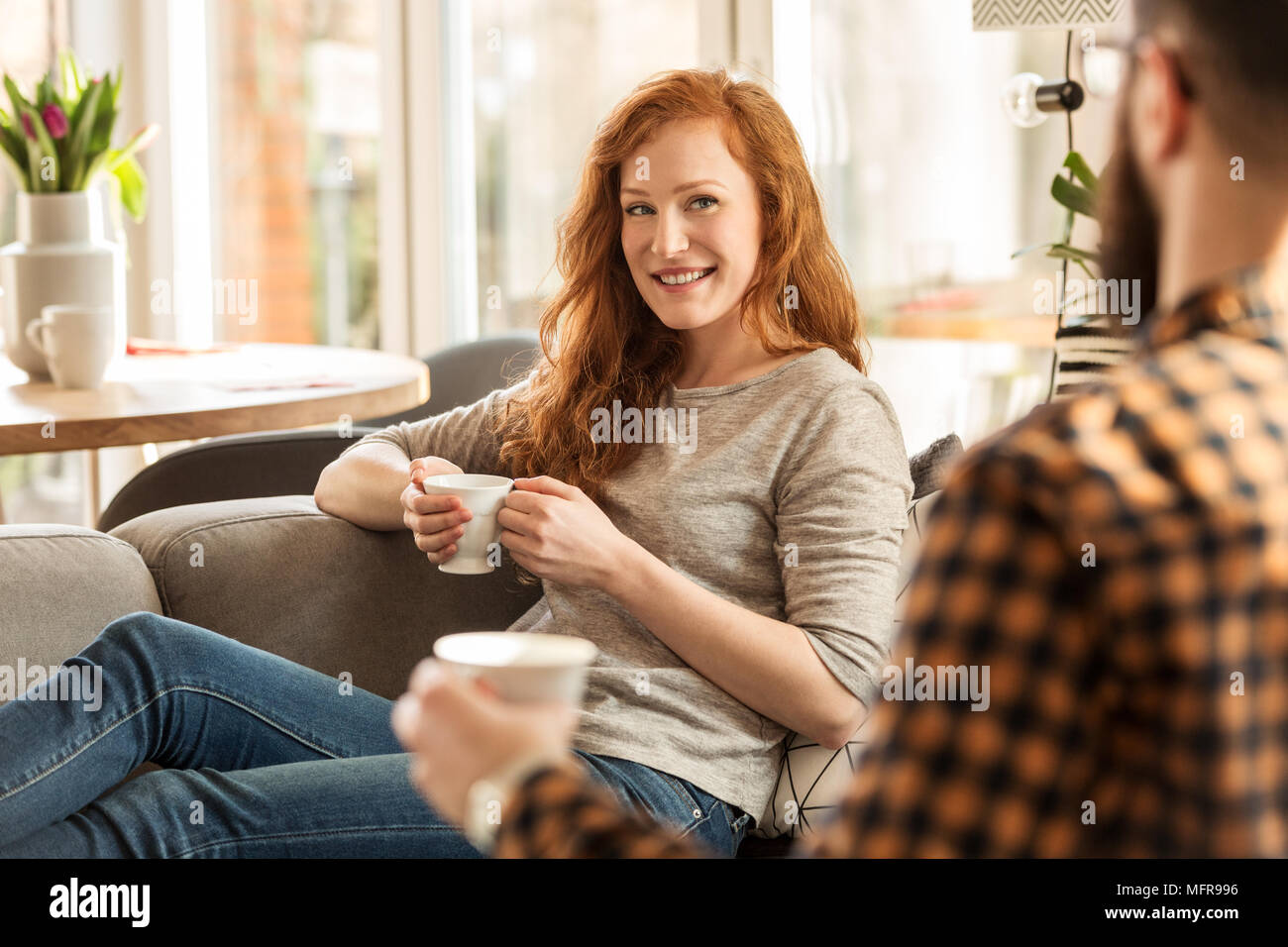 Smiling woman drinking tea and looking lovingly at her husband - Stock Image