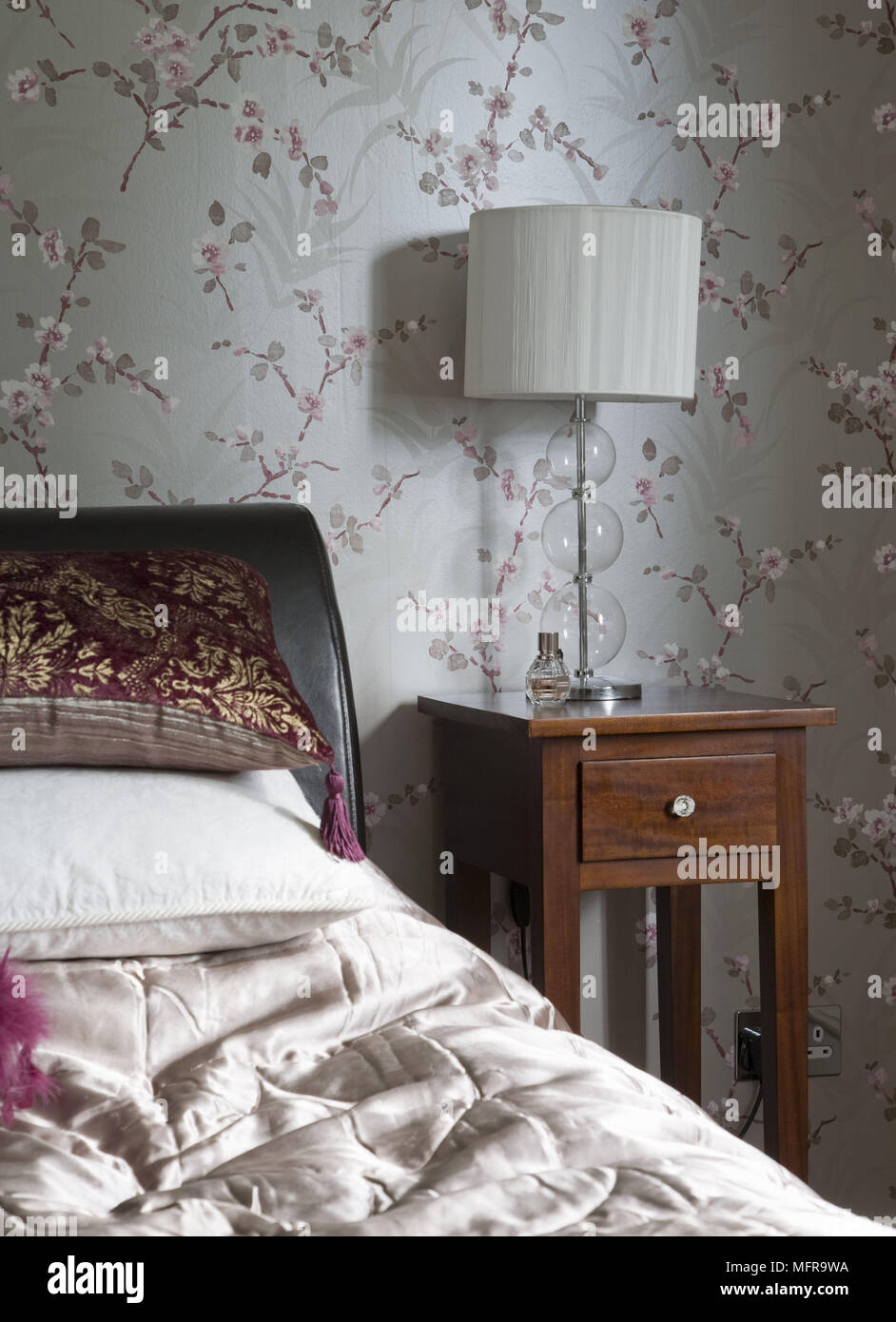 Lamp On Wooden Bedside Table Next To Bed With Leather Headboard In