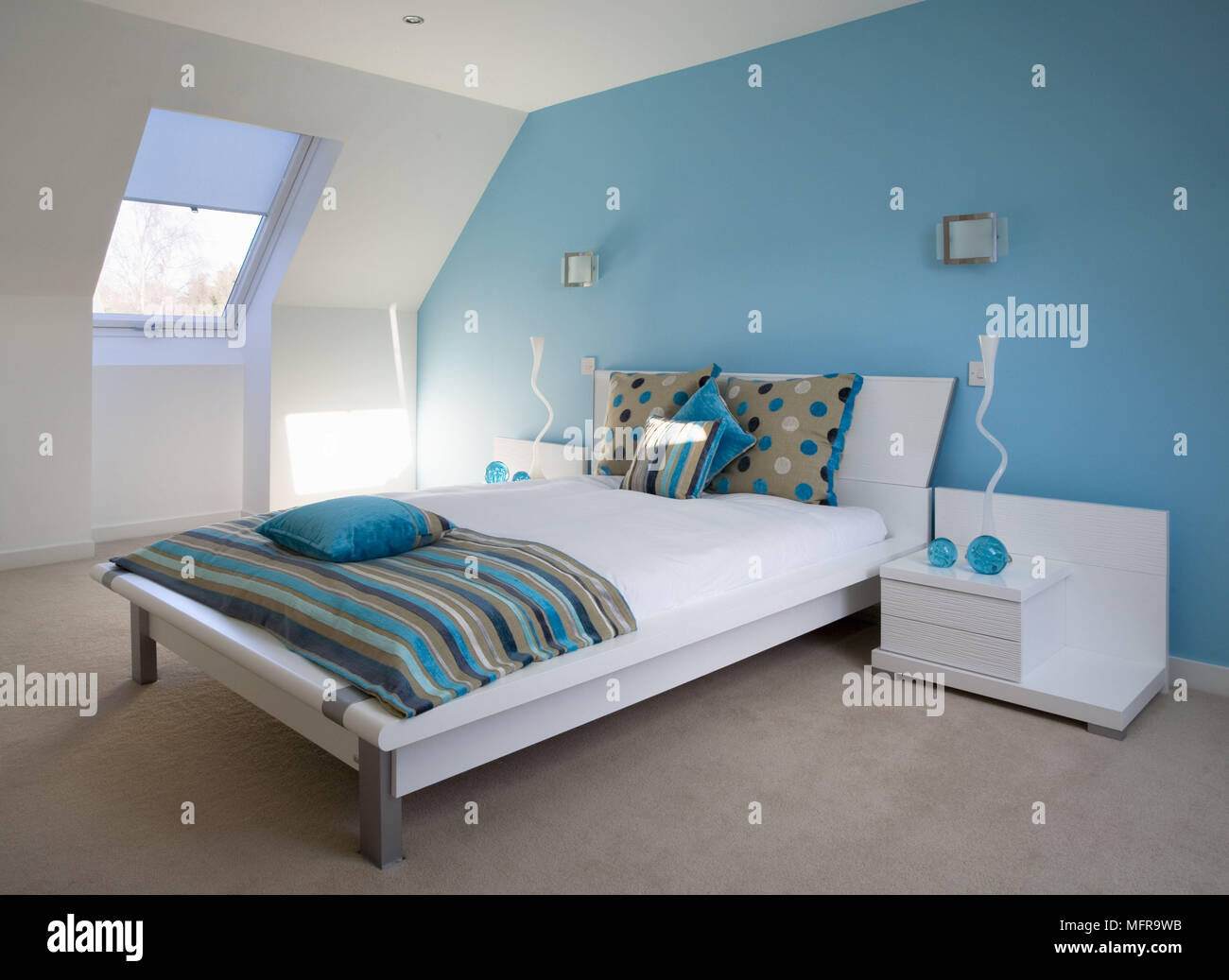 Lamps on beside units either side of double bed in contemporary blue ...