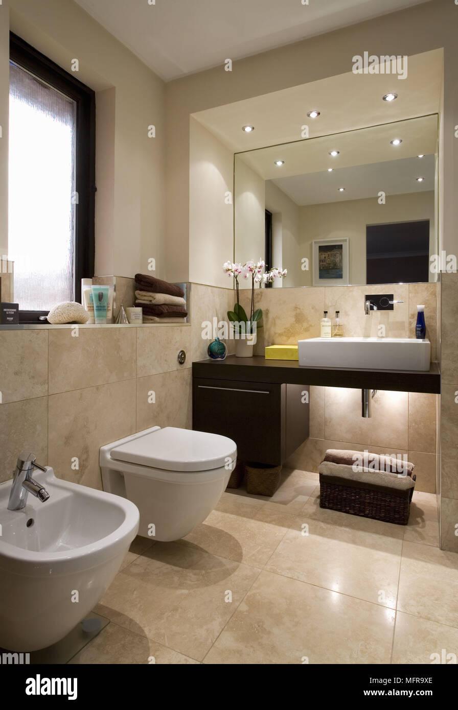 Mirror Above Washbasin Set On Shelf Unit In Modern Bathroom With Toilet And  Bidet Below Window