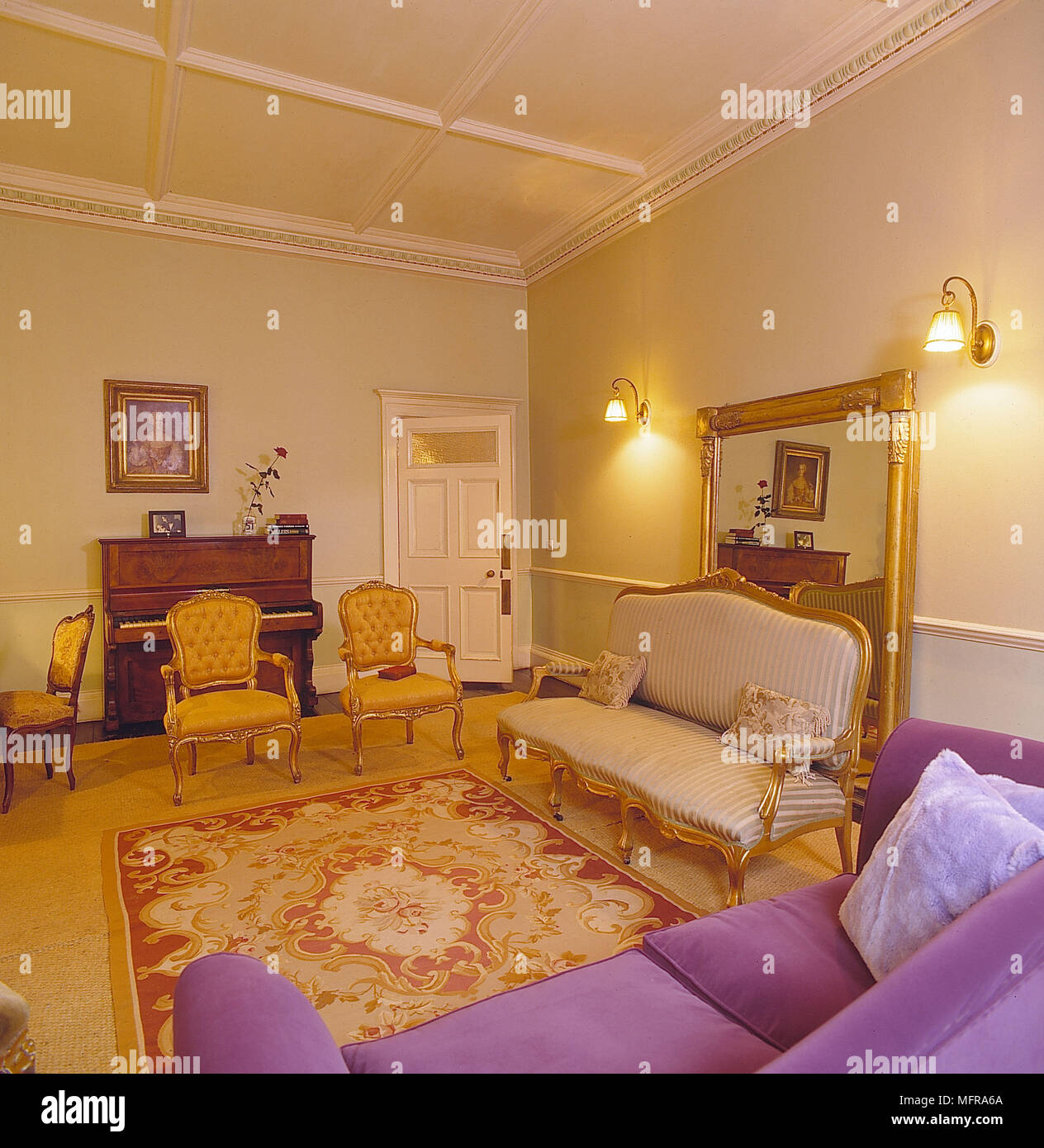 Sitting room yellow walls red rug gold carpet purple couch gold chairs piano large gold mirror ineteriors rooms antiques painting wall lights plasterw