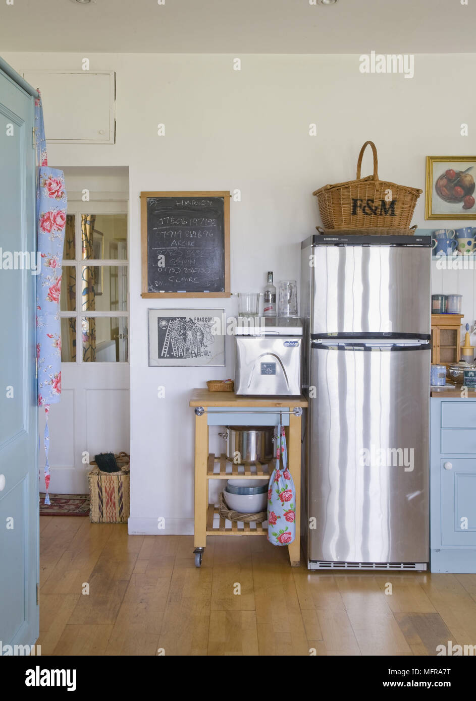 Storage Trolley Next To Stainless Steel Fridge In White And Blue Kitchen