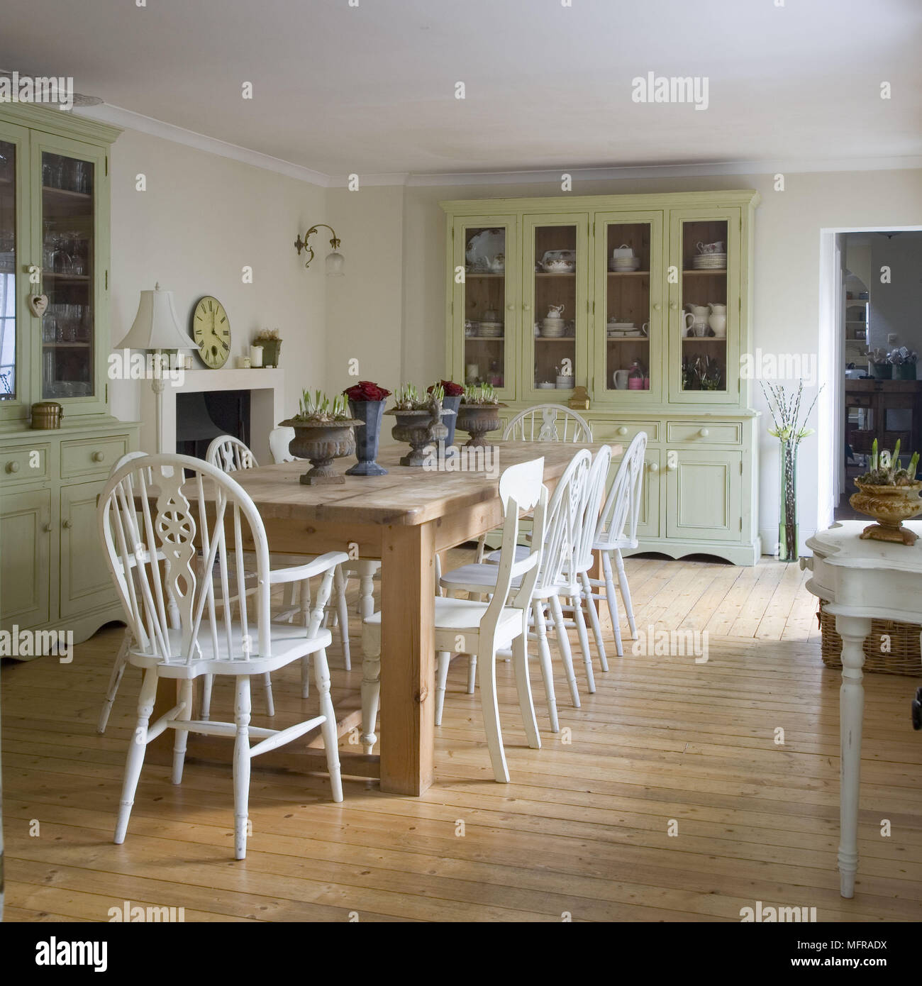 Country Style Dining Room Furniture: Wooden Table And White Painted Chairs In Centre Of Country